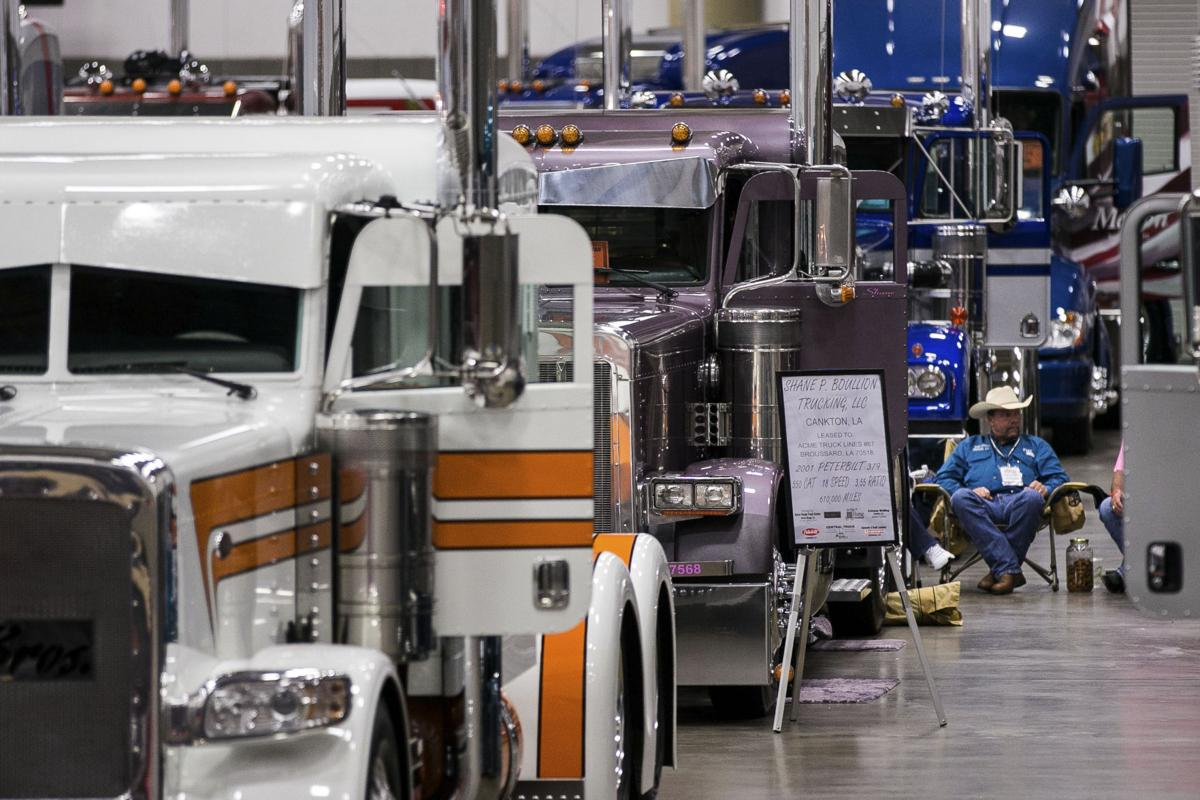 """A truck owner sits by his custom rig among entrants in the """"Pride and Polish"""" competition during the 16th annual Great American Trucking Show in Dallas on Aug. 22, 2014. MUST CREDIT: Bloomberg photo by T.J. Kirkpatrick."""
