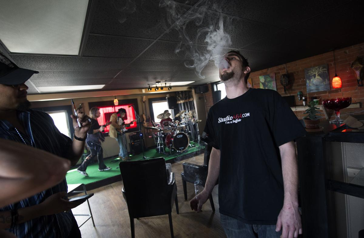 Clois Power smokes a joint inside the StudioA64 smoking lounge Tuesday, April 22, 2014, before join a group of supporters who marched to the Colorado Springs City Hall. About 50 people marched from StudioA64 to the city hall in support of the smoking lounge. (The Gazette, Christian Murdock)