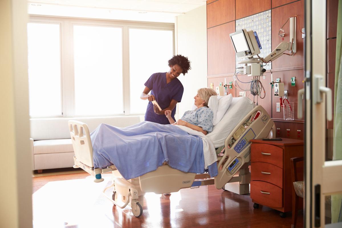 Hospital Nurse With Digital Tablet Talks To Senior Patient