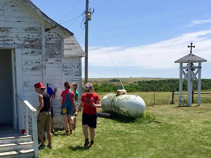 Volunteers work on the St. Paul's Episcopal Church in Norris, SD, in June 2016. The bell from this tower, at right, was stolen between Dec. 31, 2017, and Jan. 3, 2018. The tower was pulled over, and the cross at the top, a wooden carving of a Niobrara Cross, was broken into three pieces. Photo by Carrie Thomas