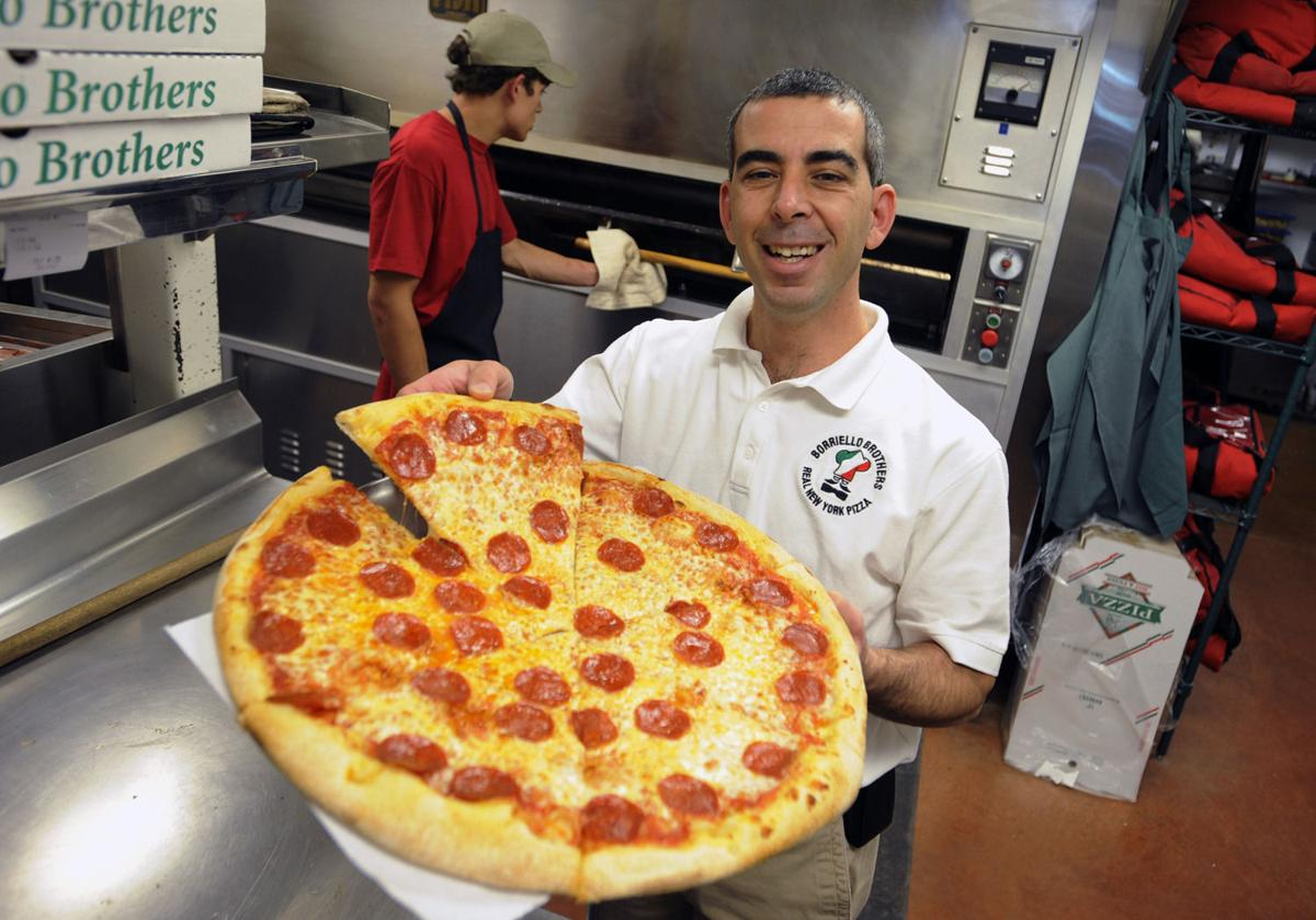 Borriello Brothers owner Rob Raia, held a piece of his pepperoni pizza at his 8th Street location 10/23/09. They specialize in New York Style pizza and have been in town since 1999. CAROL LAWRENCE,THE GAZETTE