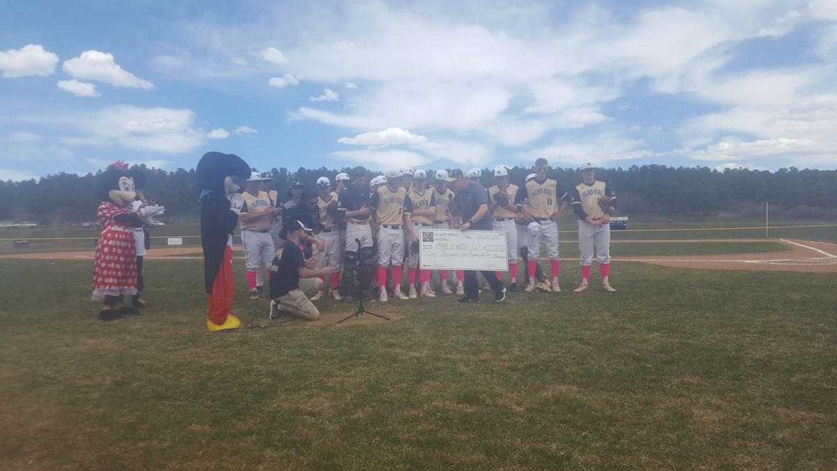 Palmer Ridge High School's baseball team presents the Gilbert family with a check