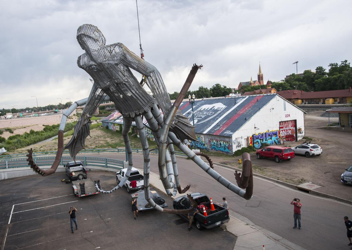 "Fort Collins artist Trace O'Connor's installation ""Iscariot,"" a giant mermaid octopus, is lifted with a crane to the top of the 234 W Colorado Ave. building Thursday, June 7, 2018. The art piece created by recycled metal and wood is part of the 20th anniversary of the Art on the Streets project in downtown Colorado Springs. O'Conner spent about four hours welding the pieces of together before lifting it into place. (The Gazette, Christian Murdock)"