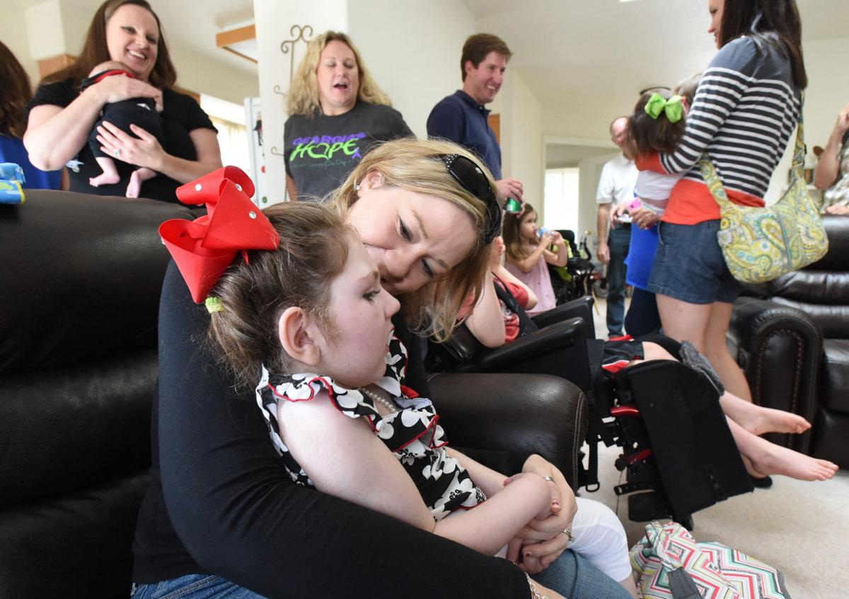 Haleigh Cox gets a kiss from her mom, Janea Cox, during a get together for families all from the state of Georgia that recently moved to Colorado Springs to treat their children with medical marijuana oil for a variety of chronic illnesses. Haleigh's Hope Act, named after Haleigh, was voted down in the state of Georgia earlier this year. The party was held at home in eastern Colorado Springs on Monday, July 28, 2014. (The Gazette/Jerilee Bennett)