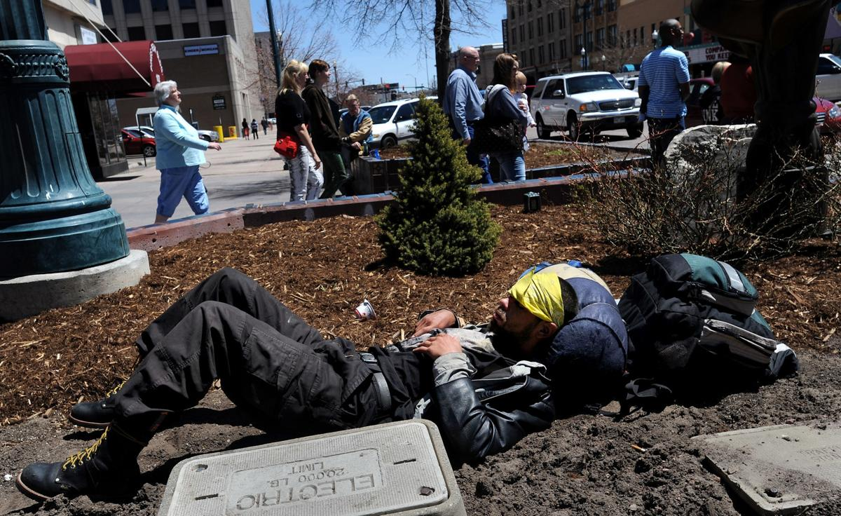 A man, who said his name was Tom, sleeps in a flower bed as pedestrians walk along Tejon Street in downtown Colorado Springs Friday, May 3, 2013, at the corner of Tejon Street and Pikes Peak Avenue. (The Gazette, Christian Murdock)