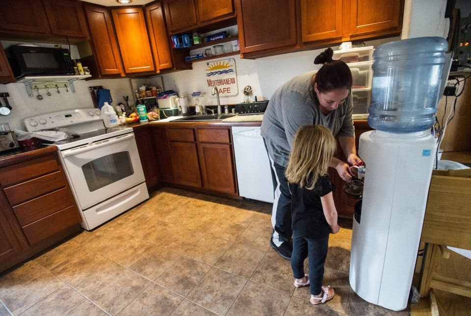 Bridgette Swaney and her daughter, Addison, 4, use the last of their bottled water to make mint tea at their Widefield home Thursday, Oct. 6, 2016. High levels of perfluorinated compounds, believed to be from a firefighting foam used at Peterson Air Force Base, have been found in the water systems of Security, Widefield and Fountain, forcing residents to drink bottled water. Swaney worries about the toxic chemicals that have been associated with kidney and testicular cancer as well as thyroid disease. Swaney and her family had drank the tap water from the day they moved into their home six years ago. (The Gazette, Christian Murdock)