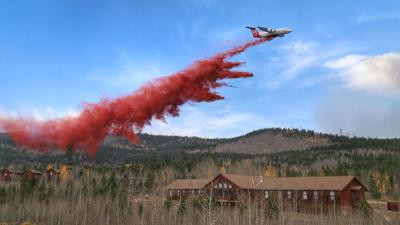 A large air tanker drops fire retardant behind the Colorado State University Mountain Campus. Photo from InciWeb.