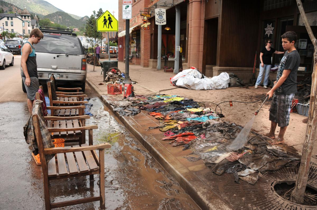 Aaron Balk,right, and Kayden Findley, both 15, help Findley's parents clean up their signs and decal shop, Stick 'Em Up, located on Canon Ave., in Manitou Springs, Monday, Aug. 12, 2013. Kayden's mom, Angie Findley ran a Ebay shop that sold clothing, from the basement, that was flooded in Friday's flash flood. Carol Lawrence,The Gazette