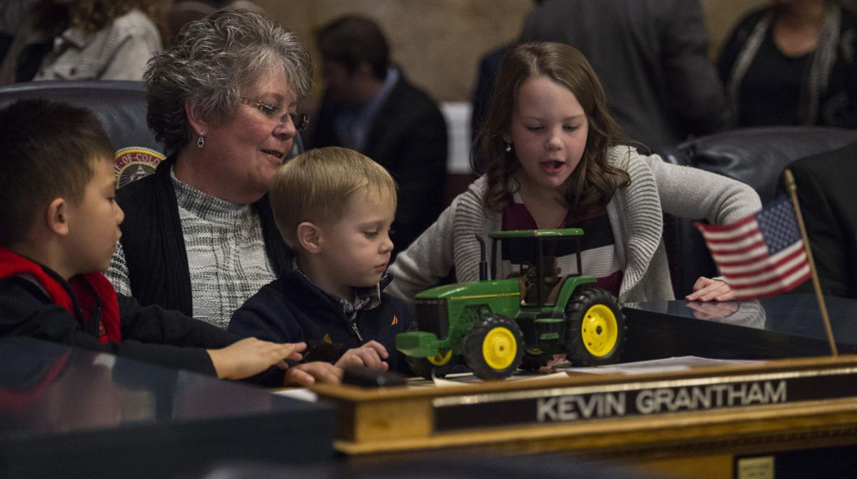 Caroline Grantham, the wife of President of the Senate Kevin Grantham, plays with her grandchildren Nathan Guo, 5, left, Samuel Grantham, 3, and Emma Grantham, 6, at her husband's desk Wednesday, Jan. 11, 2017, before the opening day of the 2017 Colorado State Legislature at the State Capitol in Denver.  (The Gazette, Christian Murdock)