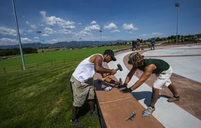 Colorado Springs Park and Rec workers Rico Barela, left, and Dominic Archuleta install skate stops Thursday, June 6, 2017, on the benches at the City of Colorado Spring's newest park, John Venezia Community Park, at the corner of Briargate Parkway and Union Blvd.. The grand opening of the ranch-themed park will be Saturday. The park will feature three large pavilions, three multi-use artificial turf fields, one in-line hockey rink, one basketball court, six tennis courts and four pickle ball courts. (The Gazette, Christian Murdock)