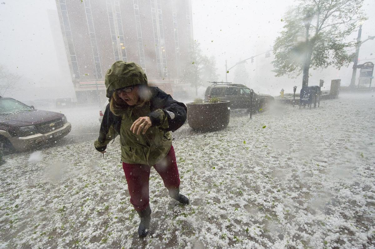 A pedestrian runs for safety as a hail storm with golf-ball size stones hits downtown Colorado Springs Wednesday, May 21, 2014. (The Gazette, Christian Murdock)