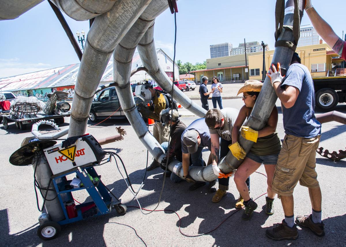 "Fort Collins artist Trace O'Connor welds together his installation ""Iscariot"" with the help of volunteers before a crane lifted the giant mermaid octopus to the top of the 234 W Colorado Ave. building Thursday, June 7, 2018. The art piece created by recycled metal and wood is part of the 20th anniversary of the Art on the Streets project in downtown Colorado Springs. O'Conner spent about four hours welding the pieces of together before lifting it into place. (The Gazette, Christian Murdock)"