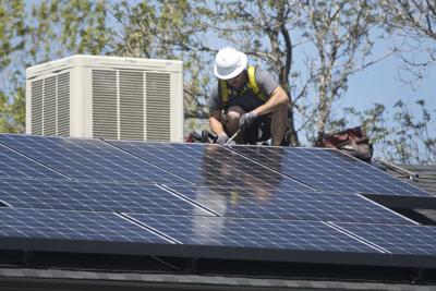 Worker installs roof top solar photovoltaic panels Denver Colorado home