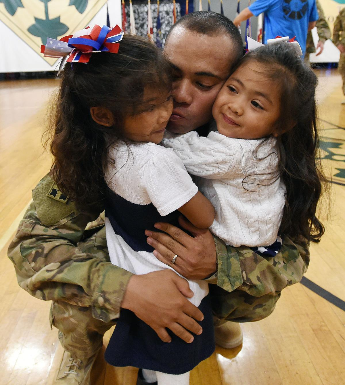 Lt. Daniel Ogelsby gives kisses to his daughters, Layla Ogelsby and Karas Oglesby during homecoming at Ft. Carson. Approximately 55 Ft. Carson soldiers from the 3rd Armored Brigade Combat Team, 4th I.D., returned from Southwest Asia on Tuesday, October 6, 2015. The troops have been gone since February. (Jerilee Bennett/The Gazette)