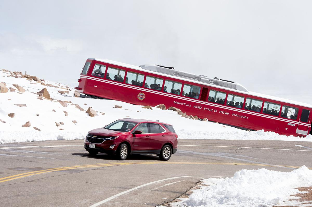 A car drives up the road to Pikes Peak while the Pikes Peak Cog Railway climbs up behind it on Friday, Sept. 29, 2017.  (The Gazette, Nadav Soroker)