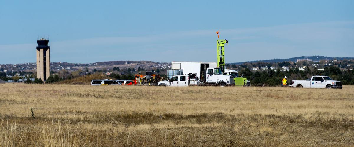 A crew drills a well next to the runway at the Colorado Springs Airport Thursday, Oct. 27, 2016, to test the water for contaminates. (The Gazette, Christian Murdock)