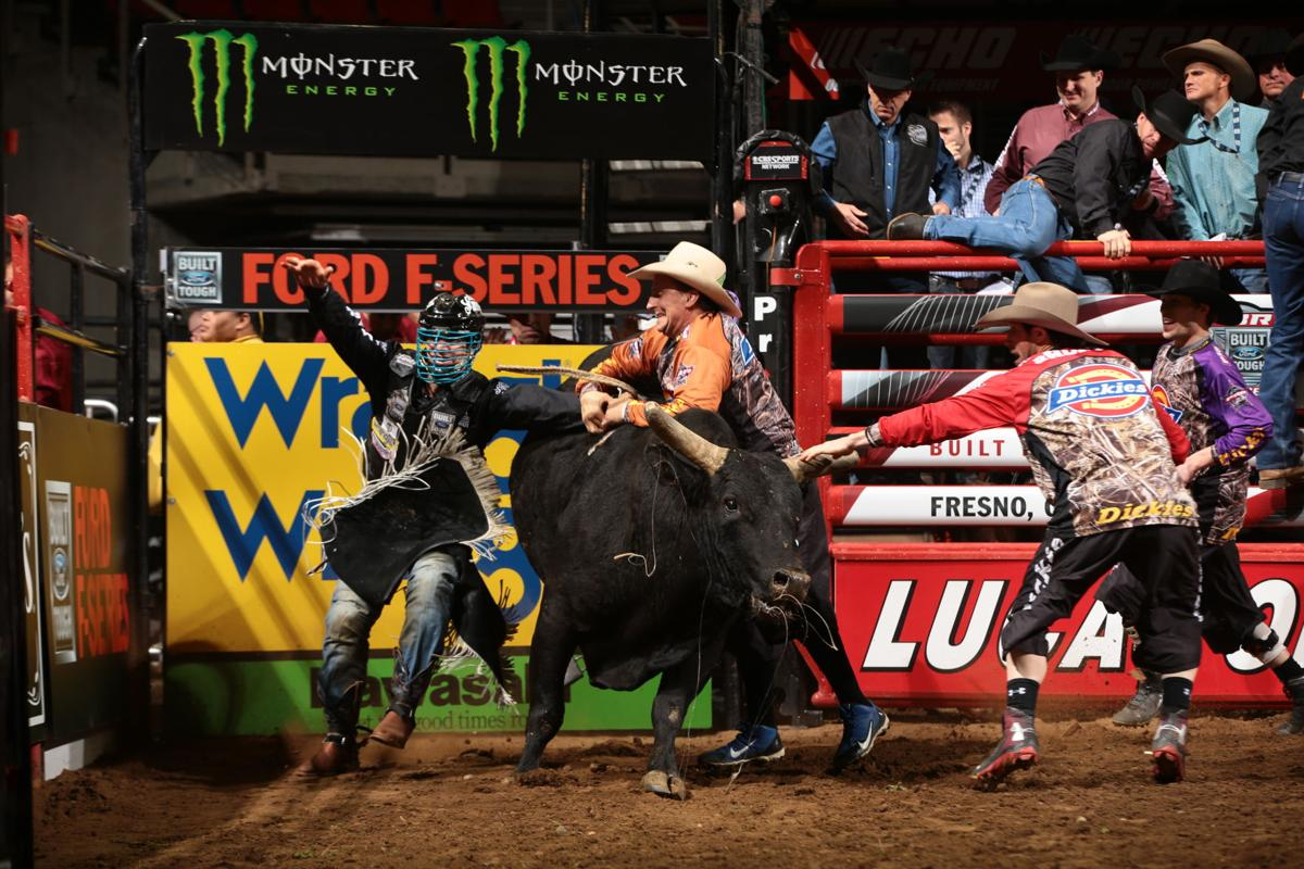 Mike Lee rides Julio Moreno's Merlot Man for 77.25 and Shorty Gorham and Frank Newsom step in to save him during the first round of the Fresno Built Ford Tough Series PBR. Photo by Andy Watson.