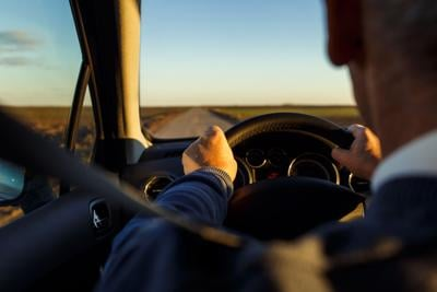 Close up of senior driver hands holding steering wheel and driving on the road.