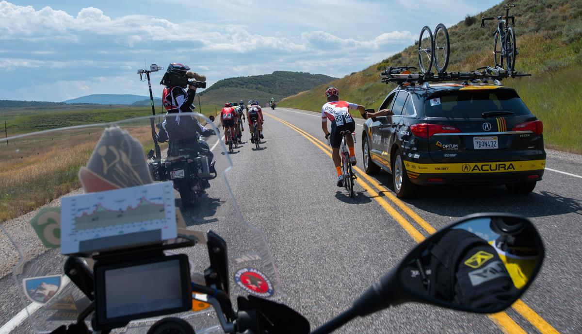 Guillaume Boivin of Optum p/b Kelly Benefit Strategies grabs supplies from support car Monday, Aug. 17, 2015, during Stage 1 of the 2015 USA Pro Challenge in Steamboat Springs, Colo. Stage 1 is a two-lap, 97 miles circuit beginning and ending in Steamboat Springs. (The Gazette, Christian Murdock)