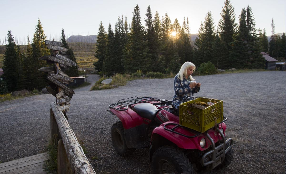 Co-owner Holly King leaves the main lodge with a hot cup of coffee before feeding the horses at Trappers Lake Lodge in northwest Colorado Thursday morning, Sept. 8, 2016. (The Gazette, Christian Murdock)