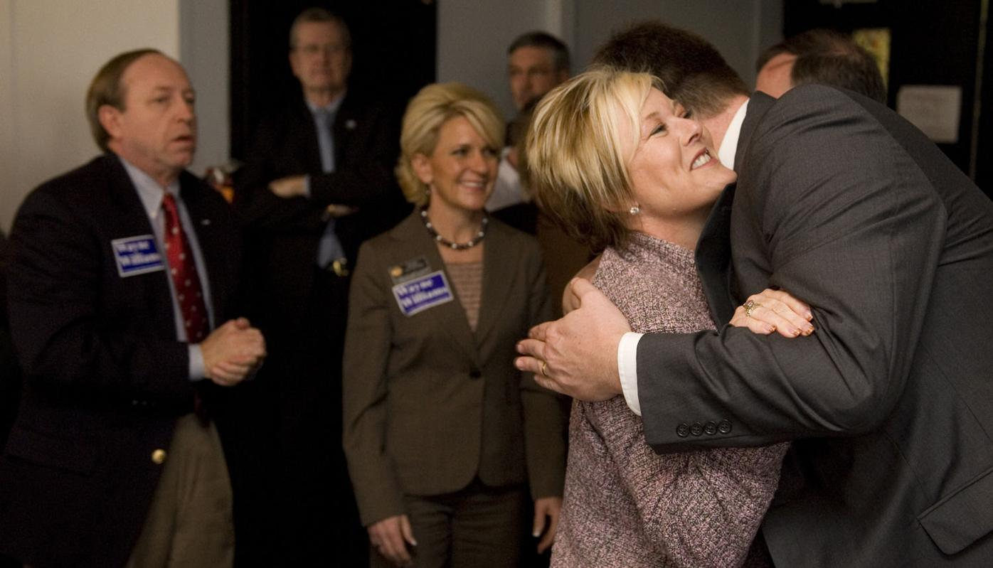 Colorado Attorney General John Suthers, left, watches as Colorado Republican Caucus Chairman Amy Stephens hugs Wayne Williams Monday, January 18, 2010 at Valley Hi during the kickoff event for Williams' campaign for El Paso County Clerk and Recorder. Mar