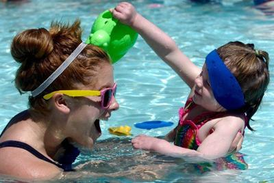 Tazlynn Brooks, 2, pours water over her swim instructor Katie Ehlers, 16, during a free learn-to-swim session at Portal Pool Saturday, May 22, 2010.The Colorado Springs Swim School will manage the Portal Pool and Wilson Ranch this summer and will haver classes in the morning and public swim in the afternoons. See www.csswimschool.com for more information. (The Gazette, Christian Murdock)