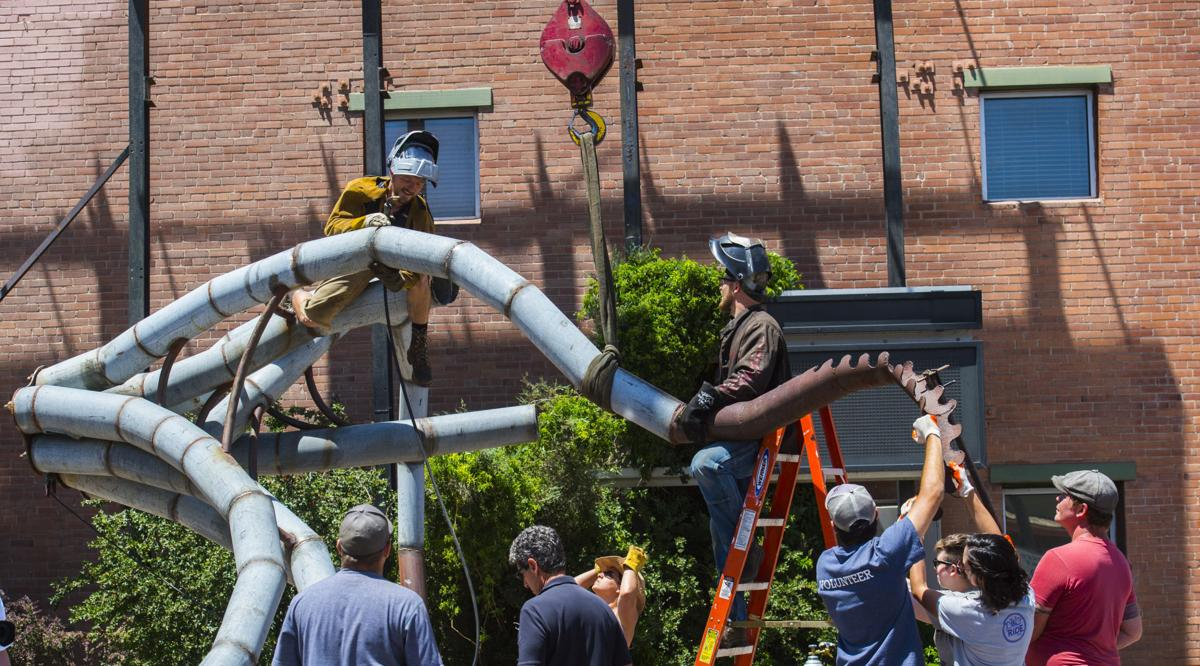 "Fort Collins artist Trace O'Connor welds together his installation ""Iscariot"" with the help volunteers before a crane lifted the giant mermaid octopus to the top of the 234 W Colorado Ave. building Thursday, June 7, 2018. The art piece created by recycled metal and wood is part of the 20th anniversary of the Art on the Streets project in downtown Colorado Springs. O'Conner spent about four hours welding the pieces of together before lifting it into place. (The Gazette, Christian Murdock)"