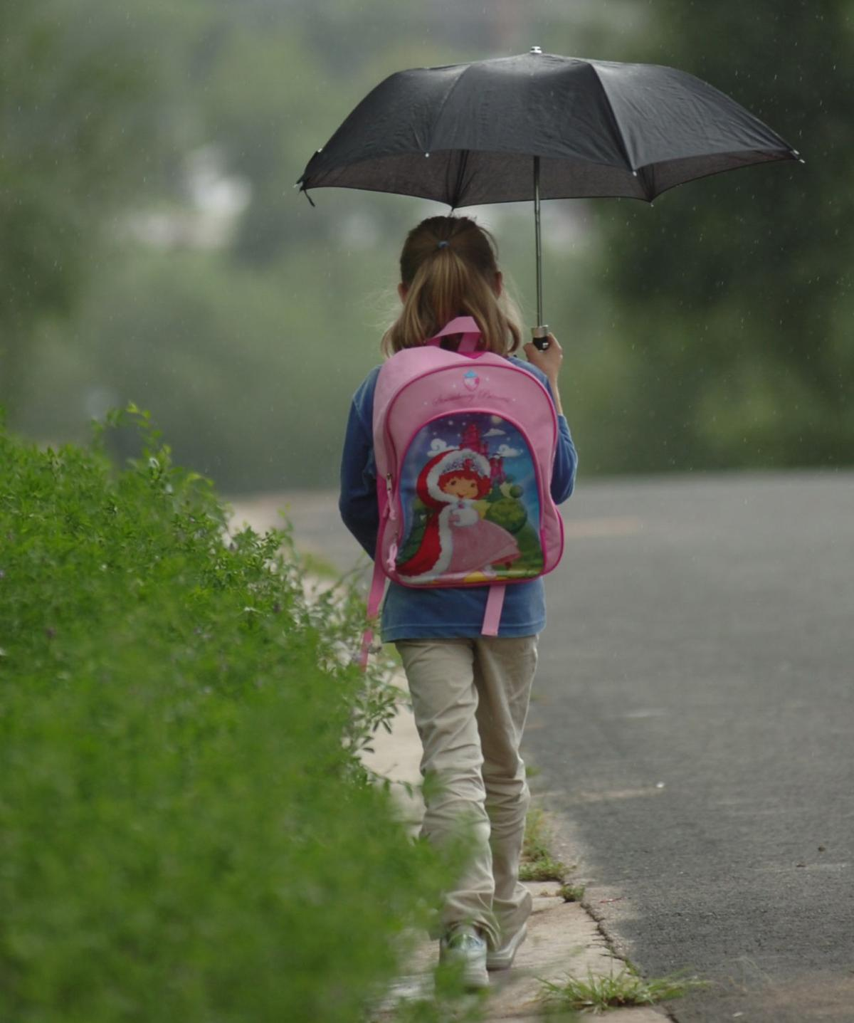 Thursday, August 24, 2006-photo by Jerilee Bennett-Krista Ellington, 7, walks home from school in a light rain storm in the Hillside community.