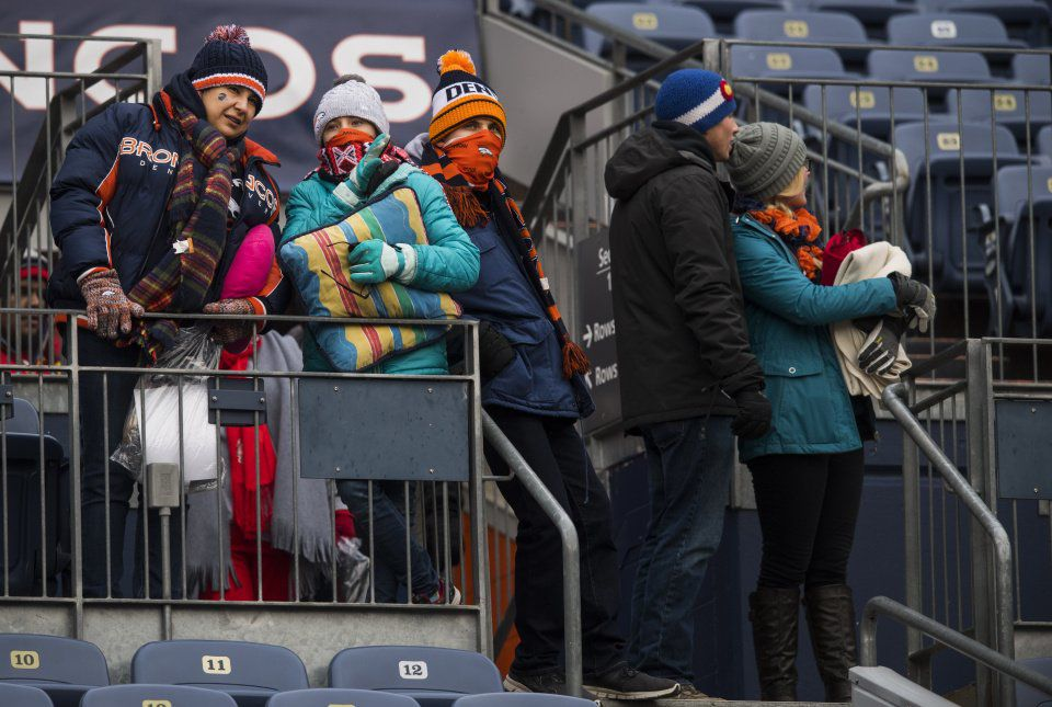 Fans arrive bundled up as the temperature on the scoreboard reads 16 degrees inside Sports Authority Field at Mile High in Denver before the start of the Denver/Kansas City game Sunday, Dec. 31, 2017. (The Gazette, Christian Murdock)