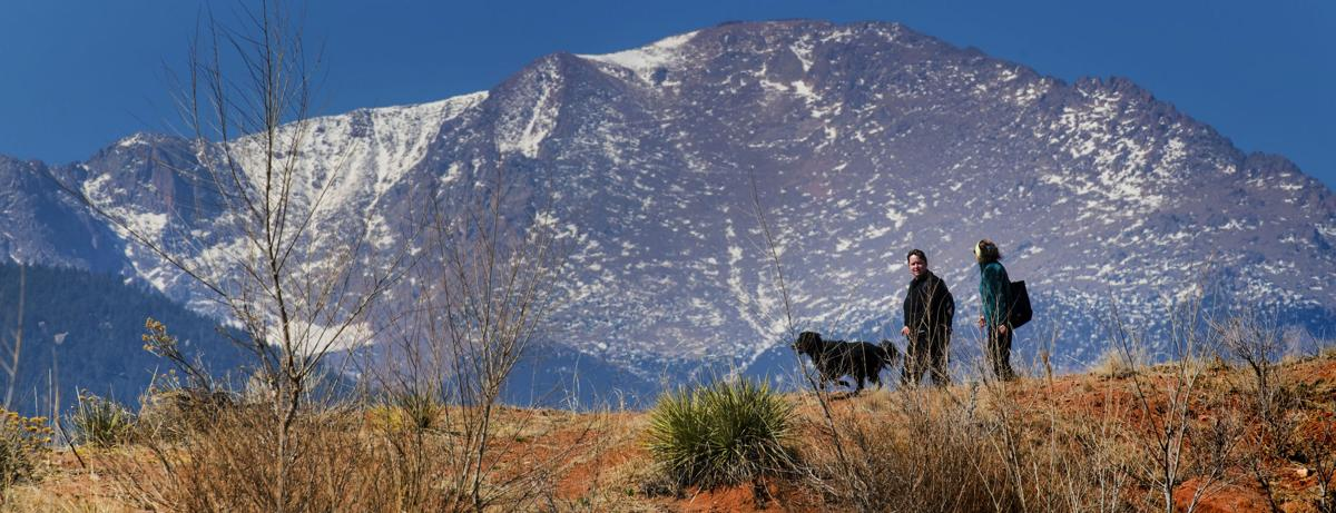 Pikes Peak, with a light dusting of snow, towers over Kristi Abbott, left, and Lynn Day as they walk with Abbott's dog, Kya, through the dog area of Red Rock Canyon Open Space after the fog cleared Monday, March 26, 2018. The weather forecast for Monday night and Tuesday calls for a chance of snow for 14,115-foot Pikes Peak and the rest of the Colorado Springs area. (The Gazette, Christian Murdock)