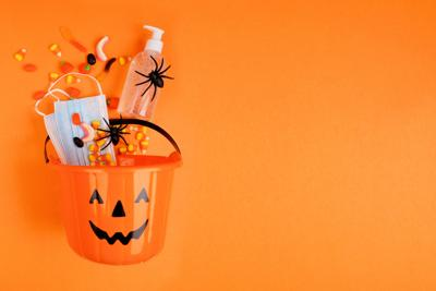 Halloween Jack O Lantern Pail With Spilling Candy And Coronavirus Prevention Supplies. Top View Over