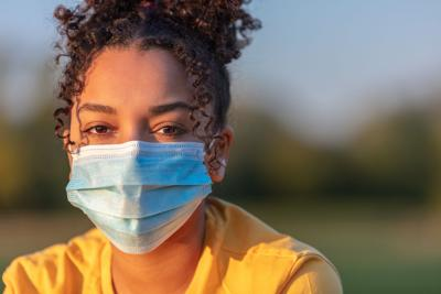 Mixed race African American teenager teen girl young woman wearing a face mask outside during the Co (copy)