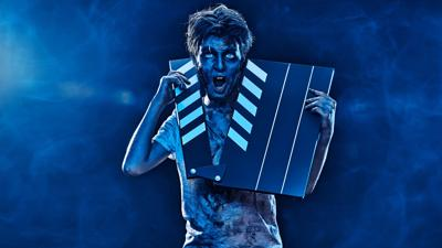 Halloween zombie boy teenager with clapperboard. Halloween movie. Copy space.