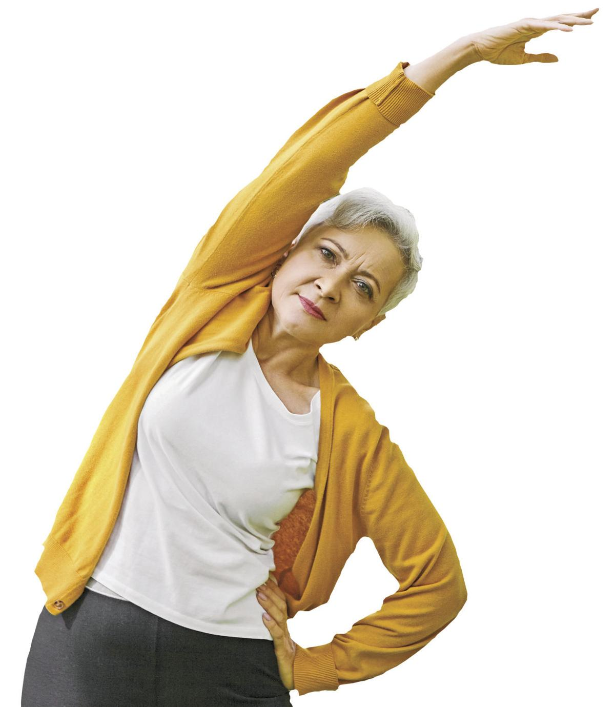 Energy, health, well being and retirement concept. Beautiful sporty senior woman with short hair doing side bend, keeping arm outstretched. Retired female exercising outdoors in park or forest