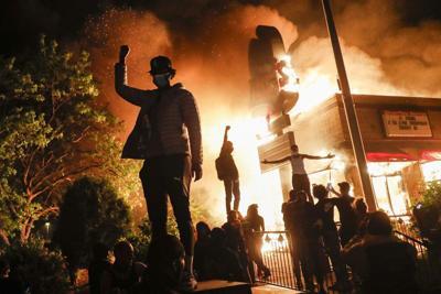 Protestors demonstrate outside of a burning fast food restaurant.