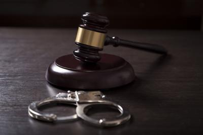 Close up of a judge gavel and handcuffs in a courtroom. (copy)