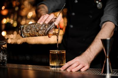 Bartender pours an alcohol cocktail adding whiskey