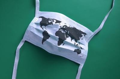 White face mask with a map of the world is lying on a green background coronavirus pandemic