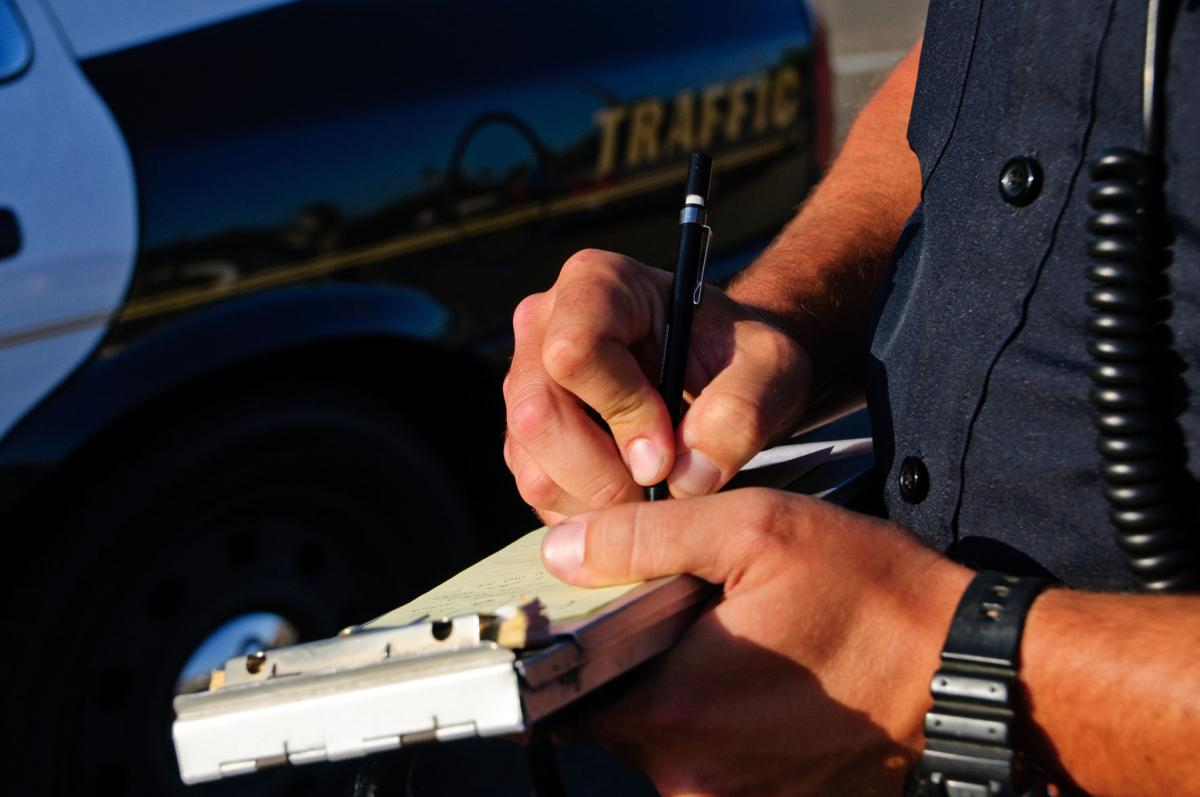 A police office on the side of the road as he writes a ticket.