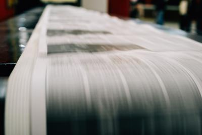 Newspaper being printed on rolls of paper