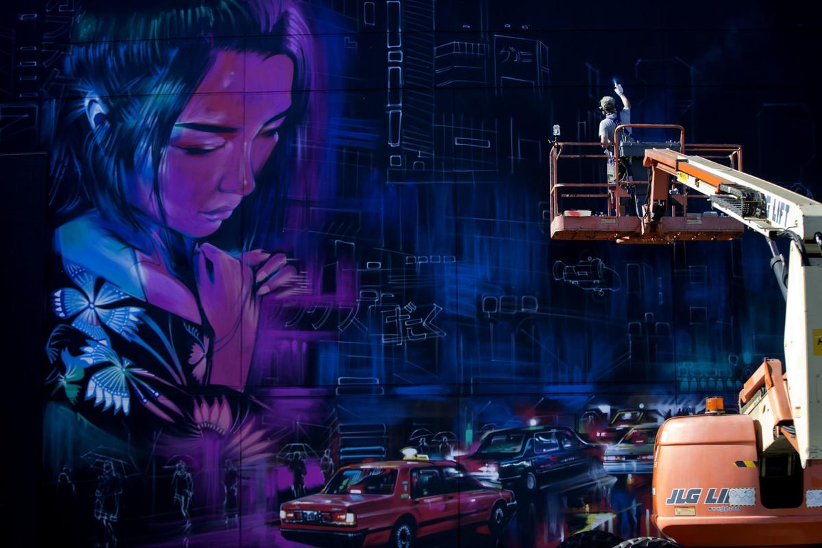 UK based artist Dan Kitchener paints a large mural on the Red Ci