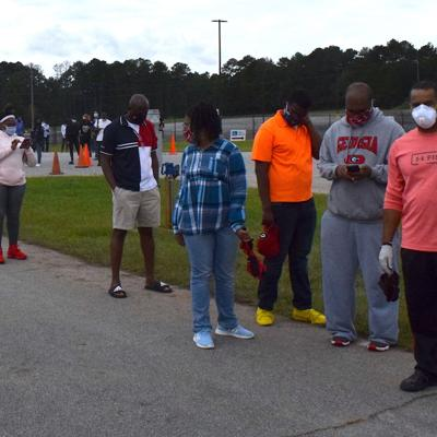 Solomon Walker second from right and kids wait in line at the Gwinnett county Fairgrounds on the first day of early voting for 2020 general election.jpeg