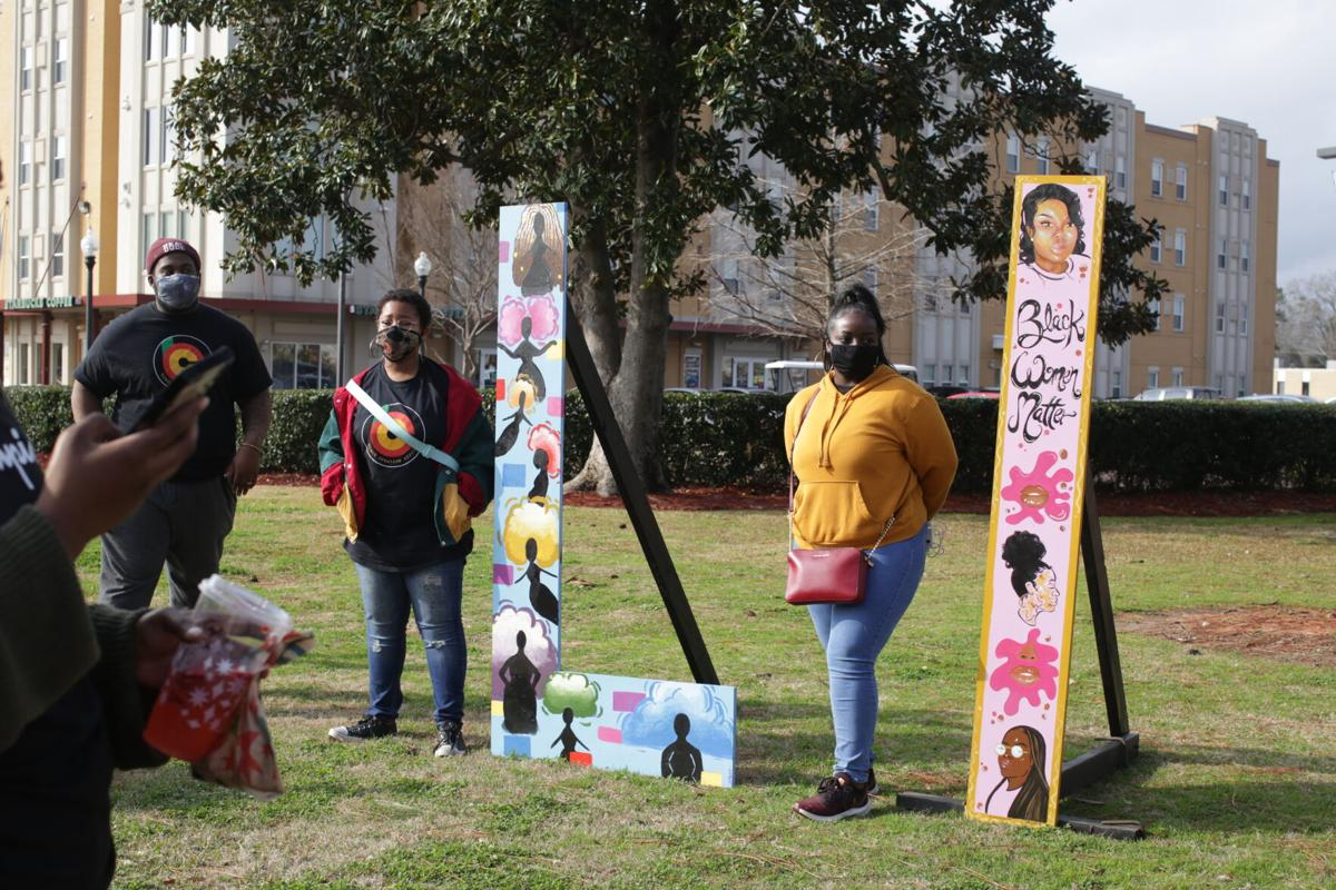 Artists stand by the letters they painted in the Black Lives Matter art installation.JPG