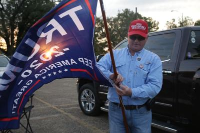 Robin Hawthorne, of Calhoun, attaches a Trump 2020 flag to a flagpole prior to the Trump rally Wednesday