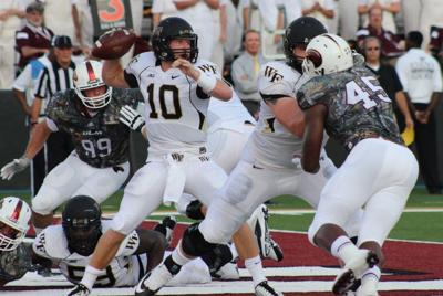 The ULM Warhawk defense provides the pass rush while the Wake Forest quarterback looks to throw from his own end zone.