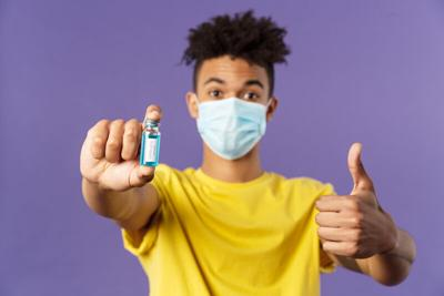 Close-up portrait of upbeat young hispanic man in medical mask holding ampoule with vaccine, coronavirus drug