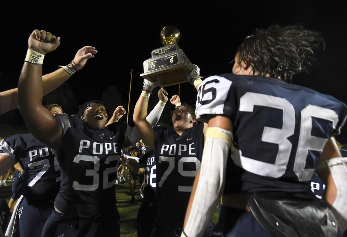 Members of the Pope John Paul II football team celebrate wit the Bishop's Trophy following their 31-17 victory Friday evening over Father Ryan.