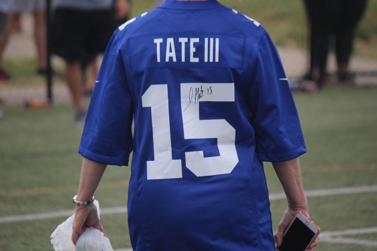 Golden Tate signs his new jersey for one of his fans during the skills camp Saturday. .JPG