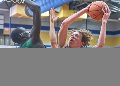 Beech's Kristian Shaw rises to the basket as his shot is blocked by Gallatin's Beljwok Adaing.