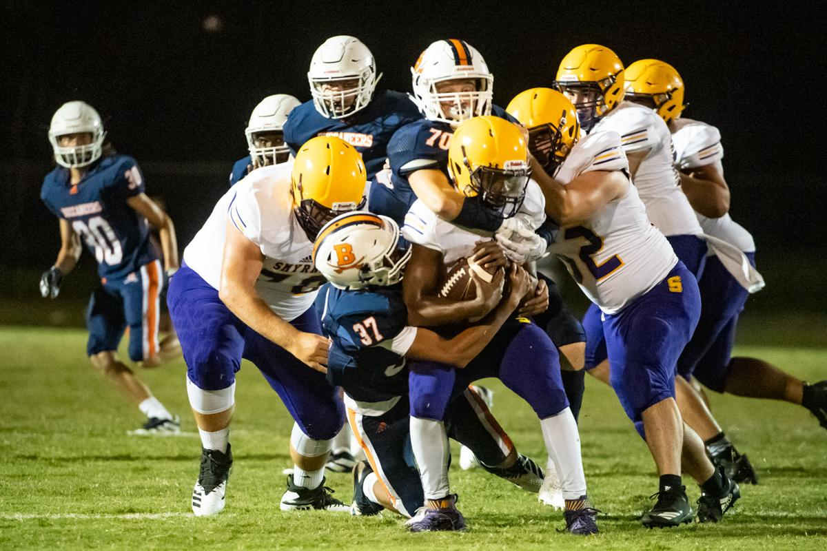 Jason Parson (37) and Austyn Keen (70) bring down a Smyrna ball carrier Friday night.